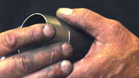 Photo of hands forming an exhaust pipe compression chamber